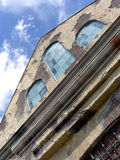 Old Building. A photograph of an old building with peeling paint and cloudy sky stock photography