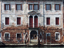 Old building alongside canal in venice with shutters and doorway Stock Photography