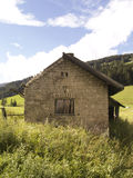 Old building - Alps. Old cabin on the green field in Alps Royalty Free Stock Photo