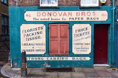 Old building with antique signage of a paper bag merchant in Shoreditch, London, UK Stock Photos