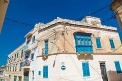 Old building in St Julians Malta on the corner of two streets. Old building with blue windows on the corner in Malta Royalty Free Stock Photography