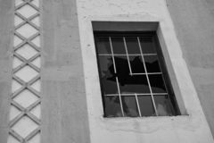 Old building with a broken window glass and a stripe pattern stock images