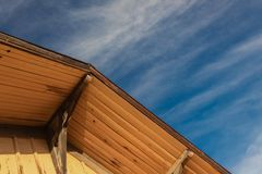 Old building construction, peak corbels and eaves, board and batten, blue sky,. Horizontal aspect stock photography