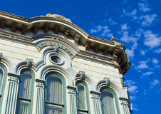 Old building corner and sky. Old building with ornate roof line and blue sky with wispy clouds in the background stock image