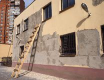 A building with damaged facade with wooden ladder by the wall royalty free stock image