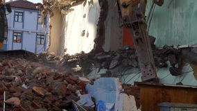Old building and debris, a construction equipment is trying to demolish the old building,