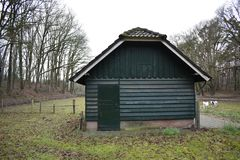 Old building in a petting zoo. An old building in a Dutch petting zoo standing in a grass field with a fence around it royalty free stock photo