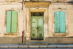 Old building elevation - vintage doors and shutters. Front facade or elevation of the old shabby building, green decorative vintage doors and wooden shutters Royalty Free Stock Images