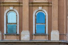 Old building facade with blue sky reflection in windows. One open window.  royalty free stock photography