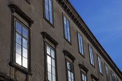 Old building facade with blue sky reflection in windows. Blue sky reflected from windows of old decaying building Stock Images