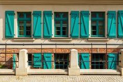 Old building facade in the center of Torun. Green window shutters. Stone old building facade in the center of Torun, Poland Stock Image