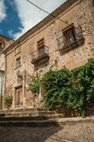 Old building facade with green creeper, on corner of narrow alley at Caceres. Caceres, Spain - July 03, 2018. Old building facade with green creeper, on corner stock image