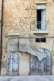 Old building facade. Old limestone building facade on sloping road stock images