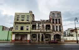 HAVANA, CUBA - OCTOBER 21, 2017: Old Building in Havana, Unique Cuba Architecture. Moving car in foreground. Old Building in Havana, Unique Cuba Architecture Stock Images