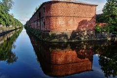 Old building on the island. An ancient building on the island. Around the channel filled with water. The water reflects the building and the blue sky. Russia Royalty Free Stock Photo