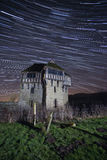 Old building at night with star trails Stock Image
