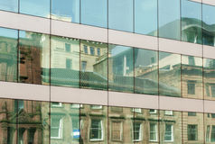 Old building reflected in modern windows Stock Photos