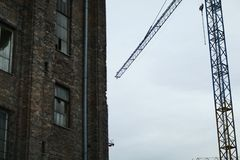 Old building renovation. Old red brick house and construction crane. Bulding renovation Stock Photography
