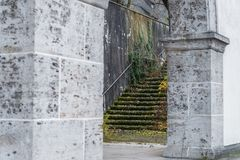 Old building ruins with stone column archway and overgrown stone stairway Royalty Free Stock Photography