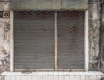 Old building with a rusty roller shutter door Royalty Free Stock Image