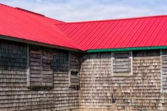 Old building with shingled walls and a red roof Royalty Free Stock Photos