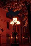 Old building, street lamp and maple tree at nigh. Night scene showing façade of an old building, sidewalk, street lamp with 4 glass balls and maple tree Stock Photos