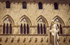 Old Tuscan building with its typical ornaments from the ancient era. Figure carved in stone in a close-up. stock photography