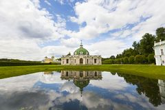 Old building - white and yellow pavilion with green roof. Old buildings - white and yellow pavilion with green roof - and their reflection in water of pond or Royalty Free Stock Photography