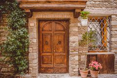 Old building with wooden doors and potted plants on street in Castel Gandolfo, Rome. Suburb, Italy royalty free stock photography