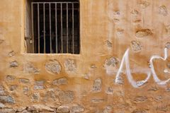 Old Building Yellow Stone Wall With  Window And Rusty Bars Stock Image