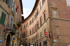 Old buildings with balcony and flags in Siena, Italy Stock Photos