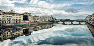 Old buildings and beautiful Ponte Santa Trinita mirrored in the Royalty Free Stock Image