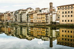 Old buildings with bell tower mirrored in the river Arno, Floren Royalty Free Stock Photo