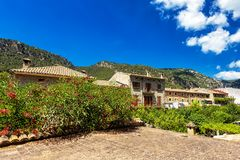 Old buildings, blooming plants and mountains in town Valdemossa, Mallorca. Spain Stock Photo