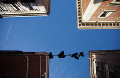 Old buildings with blue sky and hanged shoes. Stock Photography