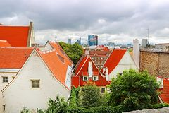 Old buildings with bright roofs in the foreground and morden buildings on the background in Tallinn, Estonia stock images