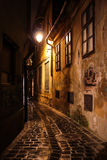 Paved street and old buildings at night Stock Photo