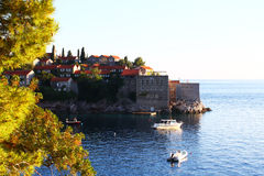 Old buildings on peninsula near trees. Old buildings of the small island of Sveti Stefan Saint Stephen with small boats near some trees Royalty Free Stock Photo