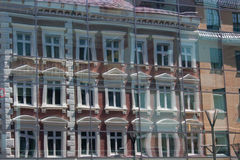 Old buildings reflecting in the windows of another buildings in t Royalty Free Stock Image