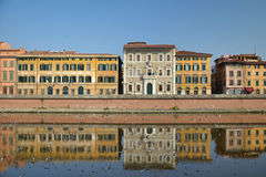 Old buildings on river shore in Pisa, Italy. Old buildings reflected on water on Arno river shore in Pisa, Italy Stock Photography