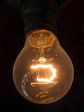 Old Bulb. Antique electric filament bulb burning with an orange glow Stock Images