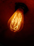 Old Bulb. Antique light bulb, filament glowing, screwed in a socket royalty free stock photography