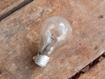 Old bulb on wooden background. Pic of Old bulb on wooden background Royalty Free Stock Image