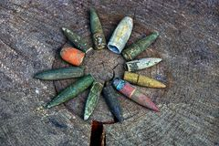 Old bullets on gray wood. Set of old colored bullets on a gray dry piece of wood Stock Photography