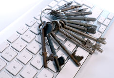 Old bunch of keys and on computer keyboard Royalty Free Stock Images