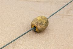 Old Buoy On The Beach. Old buoy with rope on the beach Stock Images