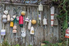 Old buoys on wooden fence. Old grunge buoys hanging on rustic wooden fence outdoors royalty free stock photo