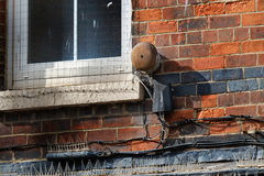 Old burglar alarm bell. Old burglar alarm bell rusting on building wall in town center stock photos