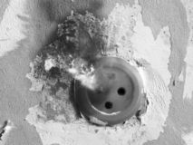 Old burned-out socket on the old wall, black and white royalty free stock image