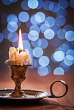 Old burning candle in vintage candlestick on wooden table Royalty Free Stock Photos